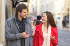 Happy couple walks in the street talking. Front view portrait of a happy couple walking in the street having a conversation royalty free stock images