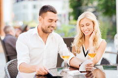 Happy couple with wallet and bill at restaurant Stock Image