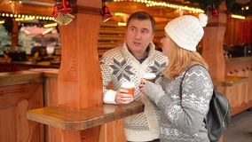 Happy Couple in Warm Clothes Drinking Coffee and Talking on a Christmas Market. Merry Christmas and Happy New Year stock video footage