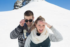 Happy couple in warm clothing in front of snowed hill Stock Photography