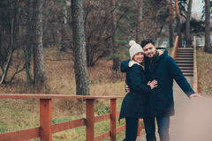 happy couple in warm knitted hat and scarf walking outdoor in autumn forest Royalty Free Stock Images