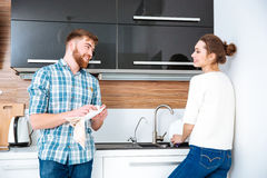 Happy couple washing and wiping diches on kitchen Royalty Free Stock Images