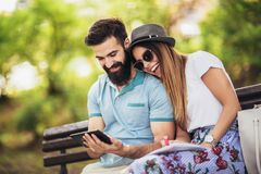 Couple watching media in a digital table outdoor royalty free stock photo