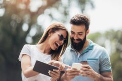Couple watching media in a digital table outdoor royalty free stock photography