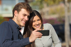 Happy couple watching media in a smart phone outdoors Royalty Free Stock Photo