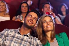 Happy couple watching movie in cinema. Happy young couple watching movie in cinema, smiling