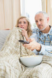 Happy couple watching a movie on the couch Stock Photos