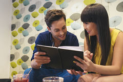 Happy couple watching social media in a notebook at bar. Royalty Free Stock Images