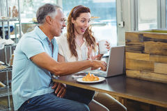 Happy couple watching something funny on laptop Royalty Free Stock Photo