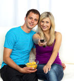 Happy couple watching television and eating crisps Stock Photography