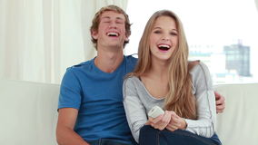 Happy couple watching the television while sitting Royalty Free Stock Image