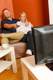 Happy couple watching television together relaxing sofa Royalty Free Stock Image