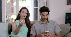 Happy couple watching television and using smartphone stock video footage