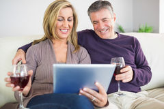 Happy couple watching their tablet pc and drinking wine Stock Images