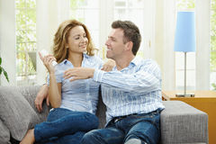 Happy couple watching TV. Young couple watching TV at home, sitting on couch, holding remote control in hand Stock Images