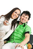 Happy couple watching TV. Smiling young couple sitting on sofa and watching TV Stock Photography