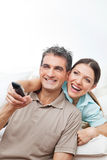 Happy couple watching TV. With remote control at home Royalty Free Stock Photo