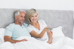 Happy couple watching tv in bed. Happy mature couple watching tv in bed at home Royalty Free Stock Image