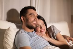 Happy couple watching tv in bed at night at home. People, family and leisure concept - happy couple watching tv in bed at night at home Royalty Free Stock Photography