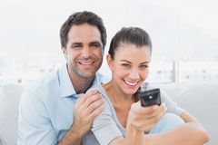 Happy couple watching tv on the couch. At home in the living room Royalty Free Stock Photos