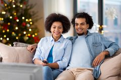 Happy couple watching tv at home on christmas. People, family and leisure concept - happy african american couple watching tv at home over christmas tree lights stock photography