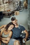 Happy couple watching TV at home. Happy loving couple resting on sofa, watching tv, laughing Royalty Free Stock Images
