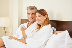 Happy couple watching TV in hotel room Royalty Free Stock Photo