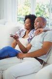 Happy couple watching tv Stock Photos