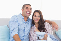 Happy couple watching TV on sofa Stock Photos