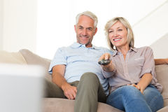 Happy couple watching tv on sofa. Happy mature couple watching tv on sofa at home Royalty Free Stock Images