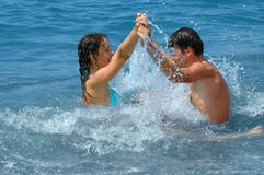 Happy couple in water. Happy young woman and man in water Stock Image