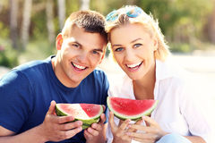 Happy couple with watermelon at the beach Royalty Free Stock Photos