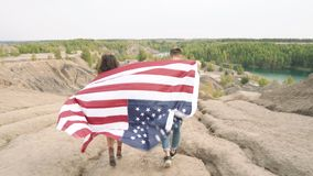 Happy couple with waving american flag running the mountains. Independence Day, lifestyle, travel concept.  stock video