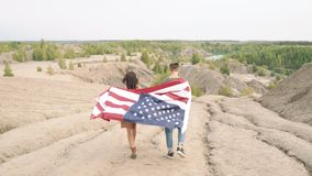 Happy couple with waving american flag walking in the mountains. Independence Day, lifestyle, travel concept.  stock video footage