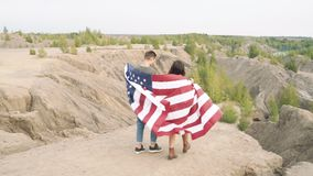 Happy couple with waving american flag walking in the wilderness. Independence Day, lifestyle, travel concept. Happy couple with waving american flag walking in stock video footage