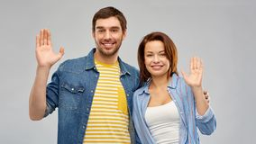 Happy couple waving hands. Greeting, gesture and people concept - happy couple waving hands over grey background royalty free stock images