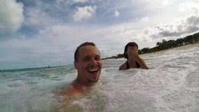 Happy Couple Waving And Swimming In Ocean. Honeymoon having fun in the ocan with big waves. Tropical island Bali stock video footage