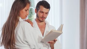 Happy couple wearing bathrobes reading a book together royalty free stock images