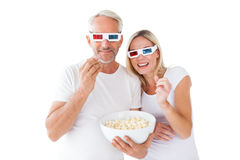 Happy couple wearing 3d glasses eating popcorn Stock Images