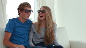 Happy couple wearing 3d glasses in front of the television stock footage