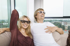Happy couple wearing 3D glasses while sitting on sofa at home Royalty Free Stock Images