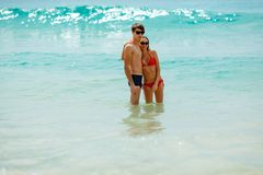 Happy couple wearing sunglasses in seawater Stock Images