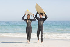 Happy couple in wetsuit carrying surfboard over the head Royalty Free Stock Photo