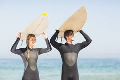 Happy couple in wetsuit carrying surfboard over head Royalty Free Stock Image