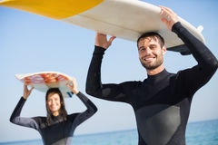happy couple in wetsuits with surfboard on a sunny day Stock Photos