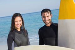 happy couple in wetsuits with surfboard on a sunny day Royalty Free Stock Image