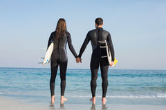 happy couple in wetsuits with surfboard on a sunny day Stock Photo