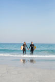 happy couple in wetsuits with surfboard on a sunny day Royalty Free Stock Photos