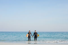 happy couple in wetsuits with surfboard on a sunny day Royalty Free Stock Photography