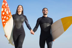 happy couple in wetsuits with surfboard on a sunny day Royalty Free Stock Photo